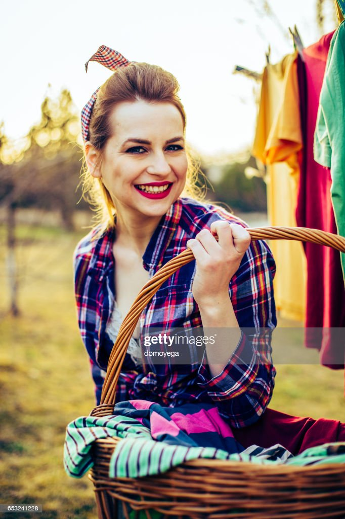Lovely retro style girl with a laundry basket outdoors : Foto stock