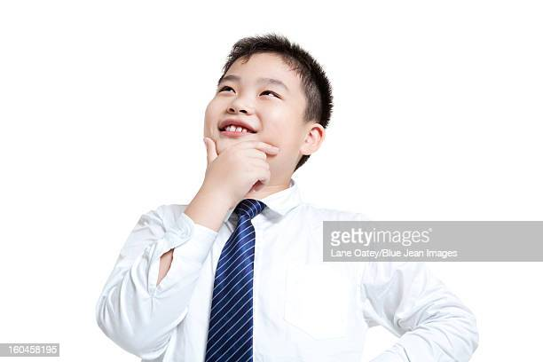 Lovely schoolboy thinking with hand on chin