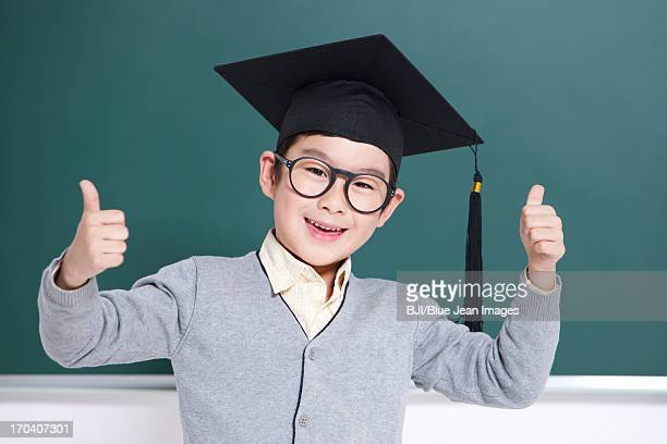 Lovely schoolboy with a mortar board doing thumbs up