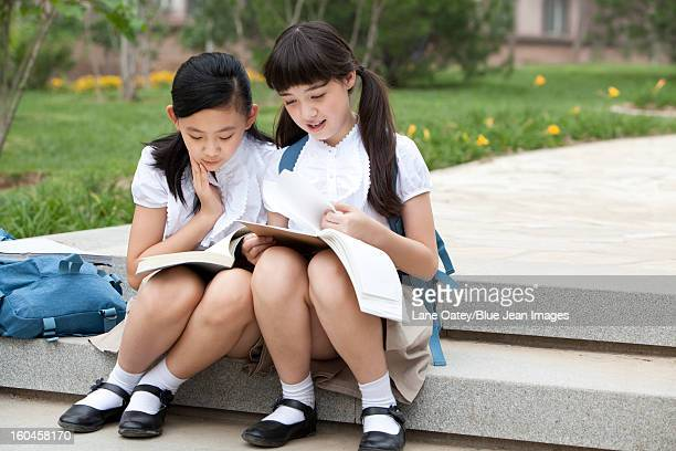 lovely schoolgirls sitting on steps and reading books outdoors - little girls up skirt fotografías e imágenes de stock