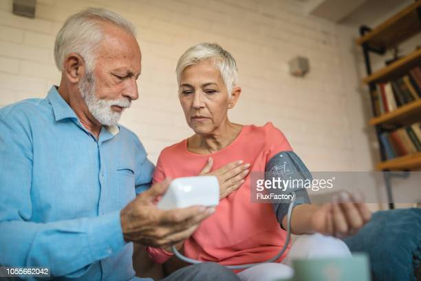 lovely senior couple measuring blood pressure - heart health stock pictures, royalty-free photos & images