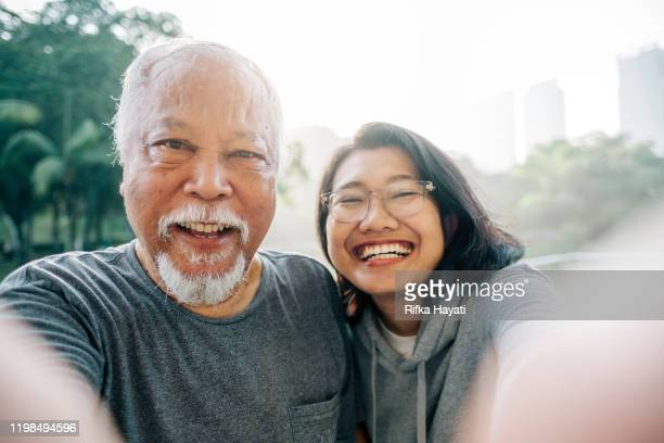 lovely senior father and daughter taking selfie together - prole adulta foto e immagini stock