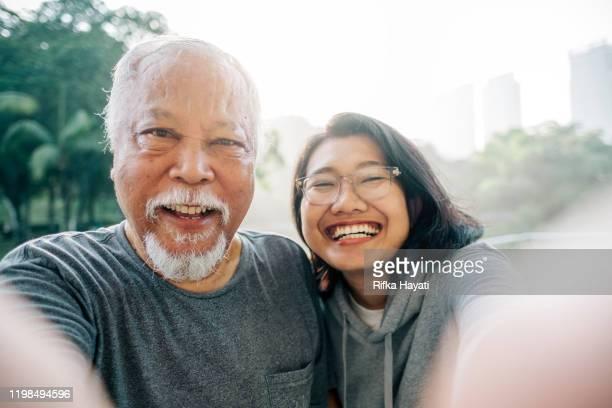 mooie senior vader en dochter nemen selfie samen - volwassen nageslacht stockfoto's en -beelden