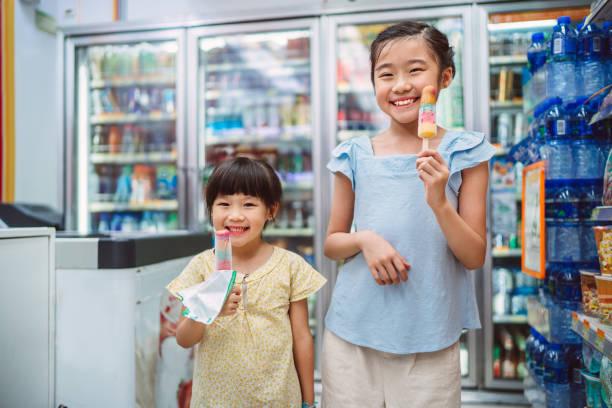 Lovely sibling enjoying popsicles in convenience store joyfully