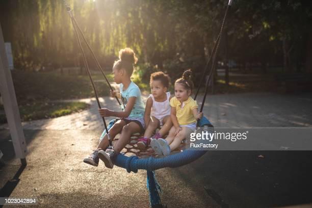 Frères et sœurs jolies jouant sur une balançoire d'aire de jeux