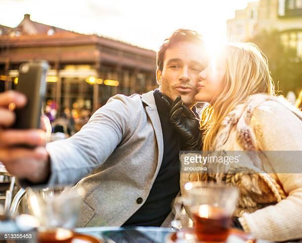 Lovely Spanish couple making selfie in Madrid Cafe
