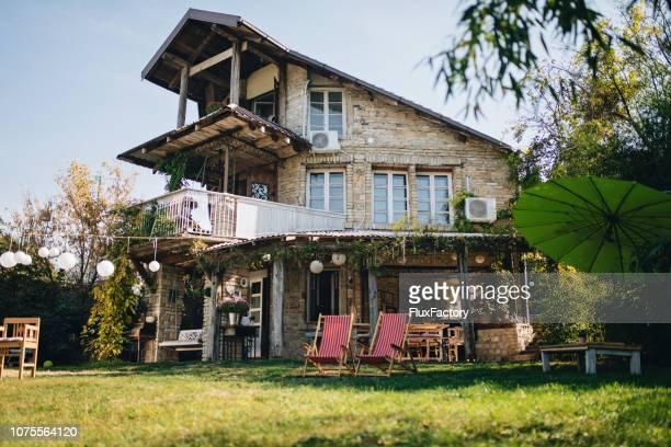 大きな前庭とポーチの振動で素敵な石造りの家 - 石造りの家 ストックフォトと画像