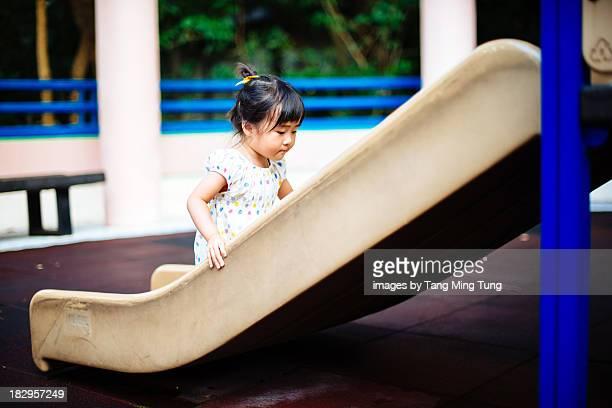 Lovely toddler girl climbing up the slide