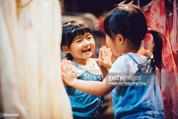 Lovely toddler girl looking at herself in a mirror