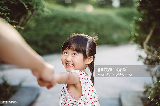 Lovely toddler leading her dad by hand