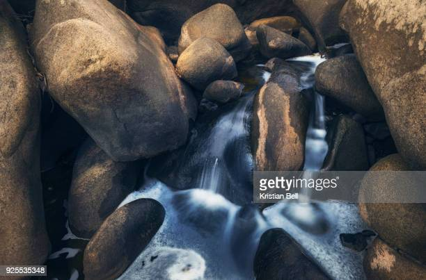 a lovely, tranquil scene on the outskirts of the city of melbourne, australia with fresh water running through a natural eroded granite rock river system. - eroded stock pictures, royalty-free photos & images