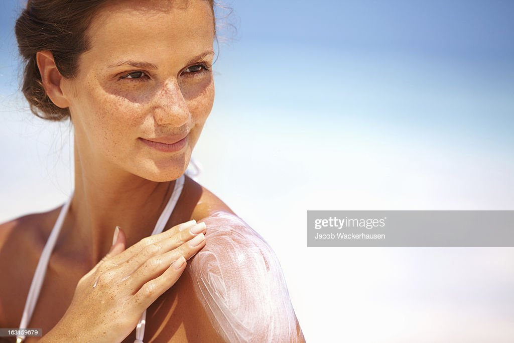 Lovely woman applying lotion : Stock Photo