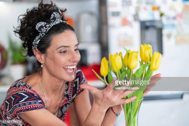 bella donna che organizza il mazzo di tulipani gialli in vaso - arrangiare foto e immagini stock