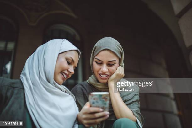 lovely woman wearing hijab looking at a mobile phone - modest clothing stock pictures, royalty-free photos & images