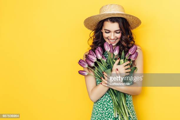 lovely woman with purple tulips bunch - yellow hat stock pictures, royalty-free photos & images