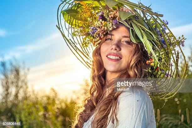Lovely young blond woman in flower wreath-hat