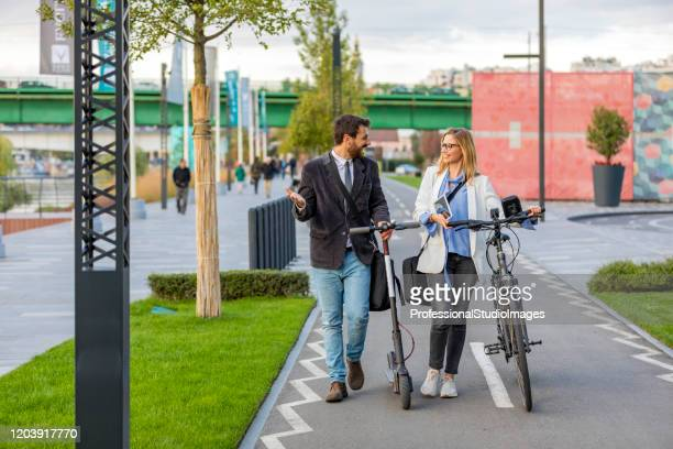 lovely young business couple with electric scooter and bicycle in the city walk. - electric scooter stock pictures, royalty-free photos & images