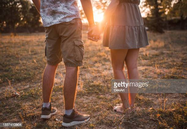 lovely young couple holding hands and looking at sunset - fiancé stock pictures, royalty-free photos & images