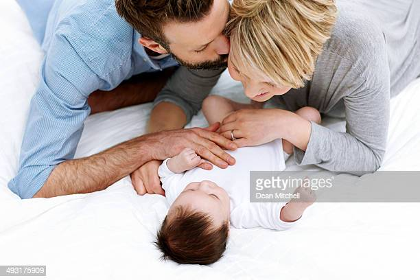 Belle jeune famille dans la chambre à coucher