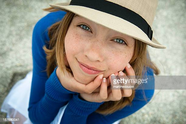 Lovely young girl with a hat looking up on beach.