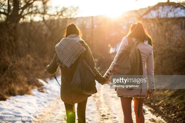mooie jonge meisjes schattige puppy wandelen - lesbische stockfoto's en -beelden