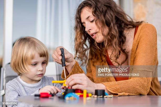 Lovely, young mother is playing with her little son with wooden toys