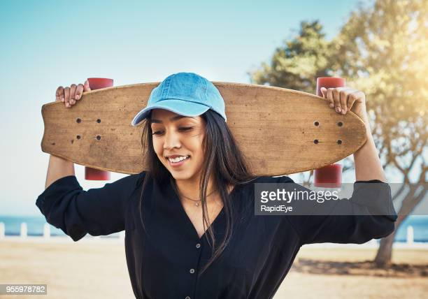 Lovely young woman with her skateboard at the seaside