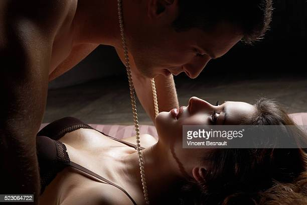 lovers connected by pearl necklace - women tied to bed stock photos and pictures