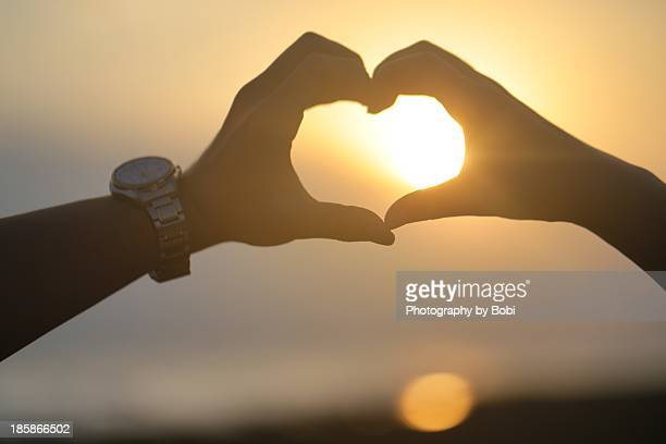 lovers hand make a heart front the sunset beach - image title stock pictures, royalty-free photos & images