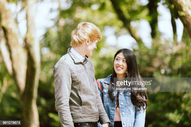 Lovers of white men and Asian women walking in a fresh green park