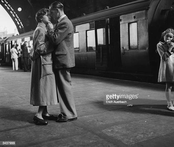 Lovers share a tender moment on a railway platform before the boat train departs.