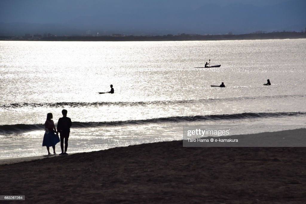 Lovers standing on the sunset beach : ストックフォト