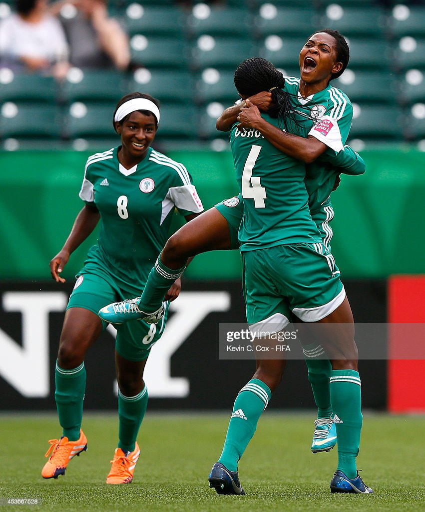 Loveth Ayila of Nigeria reacts after scoring a goal against England with Asisat Oshoala and Courtney Dike during the FIFA U-20 Women's World Cup Canada 2014 Group C match between Nigeria and England at Commonwealth Stadium on August 13, 2014 in Edmonton, Canada.
