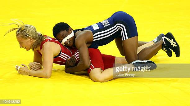 Lovina Odohi Edward holds down Jayne Clason of Scotland in the 55kg womens wrestling at the IG Sports Complex during day four of the Delhi 2010...