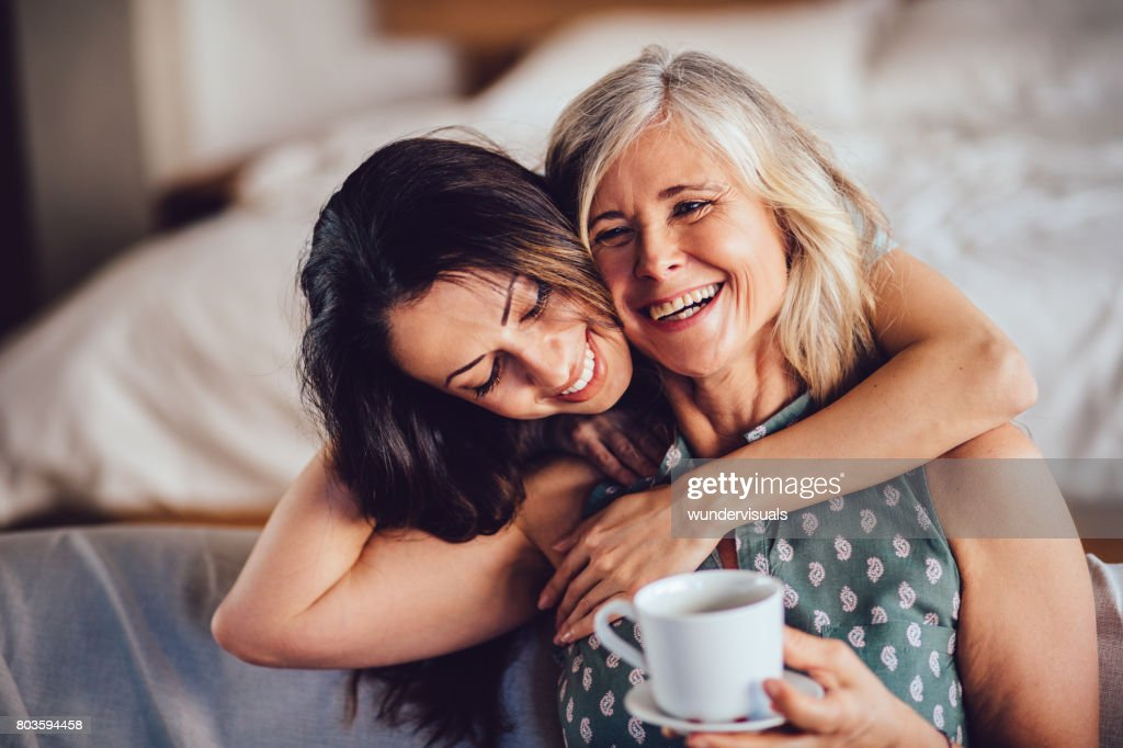 Loving adult daughter embracing cheerful senior mother at home : Stock Photo