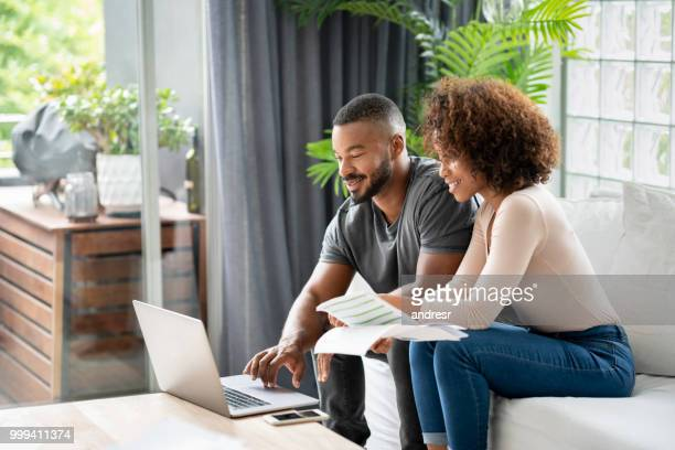 loving african american couple paying bills online at home - financial bill stock pictures, royalty-free photos & images