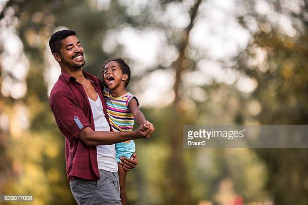 Loving African American father and daughter dancing in nature.