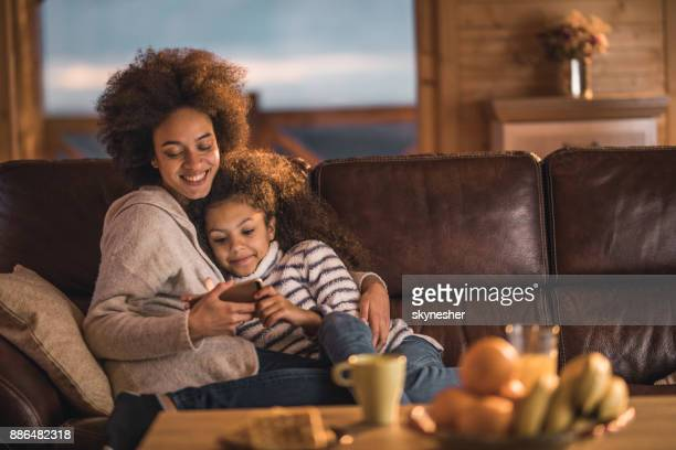 Loving African American mother and daughter watching cartoons on cell phone at home.