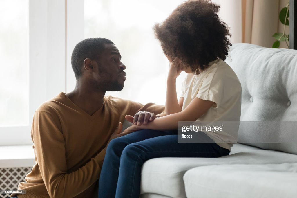 Loving african dad comforting crying kid daughter showing empathy : Stock Photo