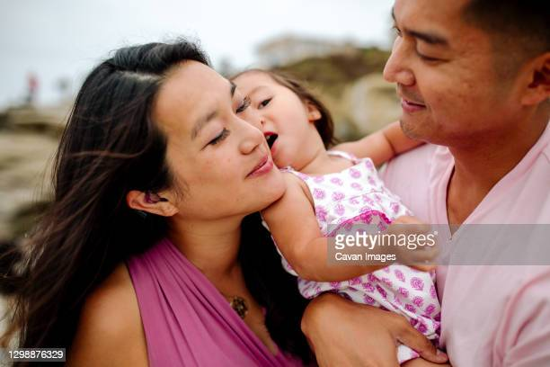 loving asian parents in pink holding young daughter between them - between stock pictures, royalty-free photos & images