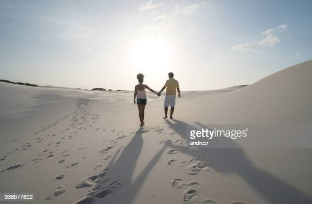 loving brazilian couple walking at the desert holding hands - lencois maranhenses national park stock pictures, royalty-free photos & images