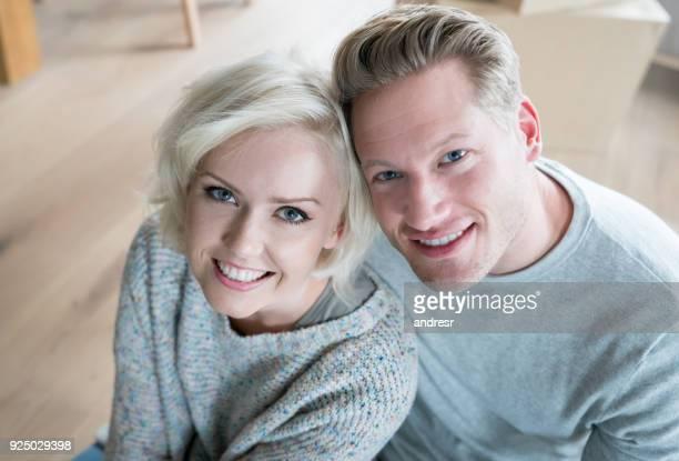Amour caucasien couple à la maison assis sur le sol en regardant sourire caméra