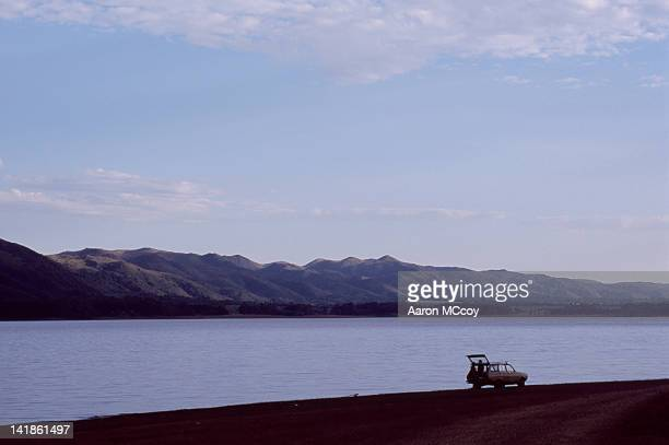 a loving couple and their car next to lago san roque near cordoba, argentina, south america - cordoba argentina stock pictures, royalty-free photos & images