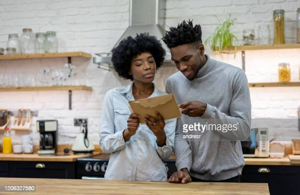 loving couple at home reading the mail - message stock pictures, royalty-free photos & images