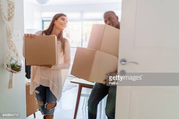Loving couple carrying boxes in new house