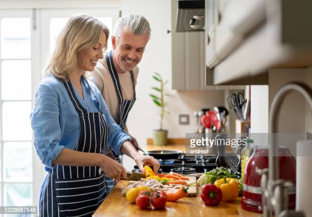 loving couple cooking together at home and looking happy - couple relationship stock pictures, royalty-free photos & images