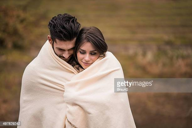 Loving couple covering with blanket while feeling cold outside.