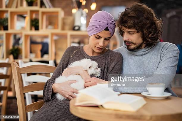 couple câlins son petit chien dans un café.