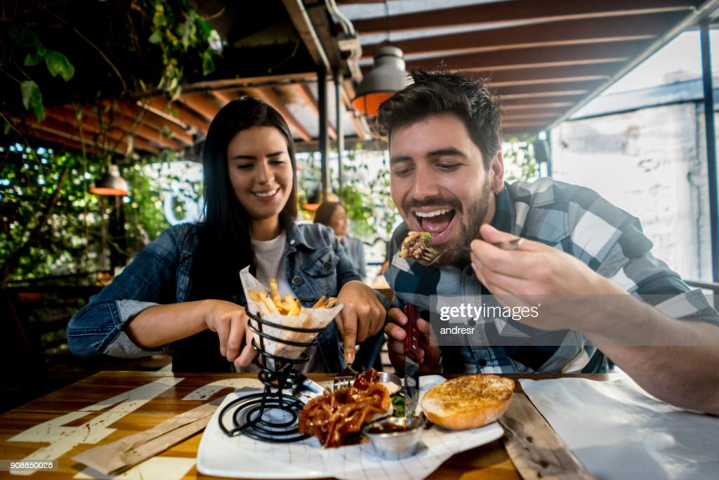 Loving couple eating together at a burger's restaurant : Stock Photo