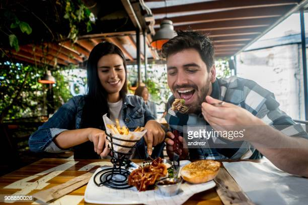 loving couple eating together at a burger's restaurant - restaurant stock photos and pictures